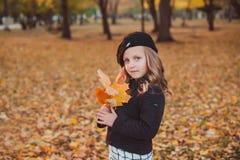 愉快的秋天 一顶红色贝雷帽的一个小女孩使用与落的叶子和笑 免版税库存图片