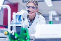 愉快的科学学生与显微镜一起使用在实验室里 免版税库存照片