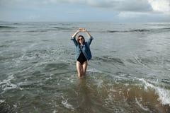 愉快的穿黑泳装和牛仔布夹克的微笑深色的妇女在海洋背景喜欢走在海洋,被举的手  库存图片