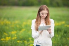 愉快的站立在与笔记本和笔的草的女孩欧洲出现 库存图片