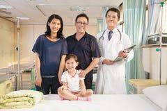 愉快的站立在病区里的家庭和儿科医生 免版税库存照片