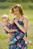 愉快的站立在领域的母亲和女儿 免版税库存图片