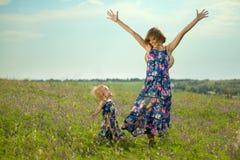 愉快的站立在领域的母亲和女儿 免版税库存照片