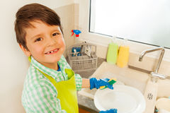 愉快的站立在水槽旁边的男孩洗涤的盘 库存照片