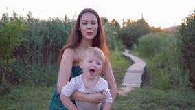 愉快的童年,年轻快乐的妈咪使用与在空气飞行在母亲手的甜男婴 股票视频