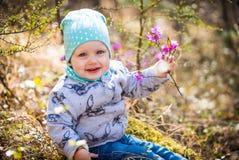 愉快的童年 户外女婴画象与迷迭香花 免版税库存照片