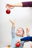 愉快的童年。男孩到达为苹果果子的儿童孩子。在家。 免版税图库摄影