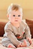 愉快的童年 有穿被编织的毛线衣的金发和蓝眼睛的逗人喜爱的小孩坐沙发和接触她的腿 免版税库存照片