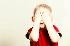 愉快的童年 白肤金发的男孩儿童孩子覆盖物面孔用手 库存图片