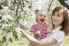 愉快的笑和使用在公园的妇女和孩子 免版税库存图片