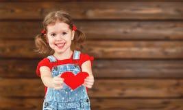 愉快的笑的儿童女孩与心脏华伦泰` s天,木 库存照片