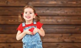愉快的笑的儿童女孩与心脏华伦泰` s天,木 免版税库存图片