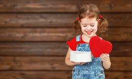 愉快的笑的儿童女孩与礼物华伦泰` s天,木 库存照片
