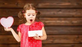 愉快的笑的儿童女孩与礼物华伦泰` s天,木 免版税库存照片