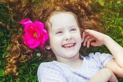 愉快的笑的女孩与在她的在绿草的头发起来了 图库摄影