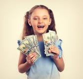 愉快的笑的富有的孩子女孩在手上的拿着金钱 葡萄酒 库存照片