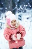 愉快的笑的小孩女孩在一个美丽的多雪的冬天森林里 库存照片