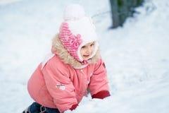 愉快的笑的小孩女孩在一个美丽的多雪的冬天森林里 免版税库存照片
