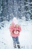 愉快的笑的小孩女孩在一个美丽的多雪的冬天森林里 免版税库存图片