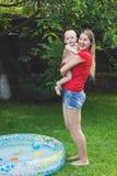 愉快的笑的母亲画象有男婴的在游泳在可膨胀的游泳池以后 免版税图库摄影