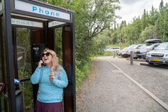 愉快的笑的白肤金发的妇女在输送路线电话亭电话谈话 库存图片