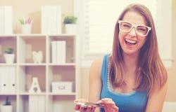 愉快的笑适合的少妇,当使用她的手机时 库存图片