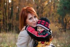 愉快的系列、母亲和儿子在秋天森林里 免版税库存图片