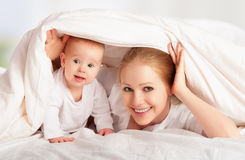愉快的系列。 使用在毯子之下的母亲和婴孩 免版税库存图片