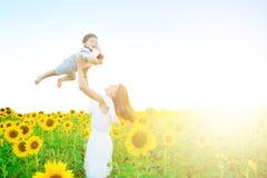 愉快的系列户外 母亲投掷婴孩,笑,并且使用在向日葵在自然的夏天调遣 免版税库存照片