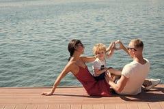愉快的系列 做心脏或爱姿态用手的母亲和父亲在他们的孩子附近 愉快的家庭花费时间 免版税图库摄影