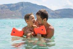 愉快的系列 年轻父亲和他美丽的微笑的儿子获得的男婴在海滩的乐趣海,海洋 正面人 库存图片