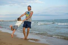 愉快的系列 年轻美丽的父亲和他微笑的儿子获得的男婴在海滩的乐趣海,海洋 正面人的emotio 库存照片