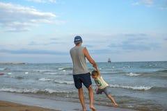 愉快的系列 年轻美丽的父亲和他微笑的儿子获得的男婴在海滩的乐趣海,海洋 正面人的emotio 免版税库存图片