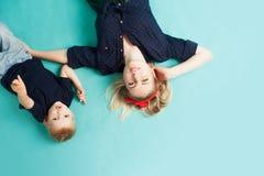 愉快的系列 有乐趣儿子的年轻美丽的白肤金发的妇女 谎言,从上面的看法 免版税图库摄影