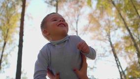 愉快的系列 母亲拿着她的她的胳膊的,儿童微笑儿子 在太阳和天空愉快的儿童` s的背景 股票视频