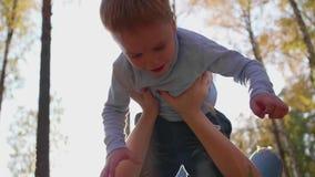 愉快的系列 母亲拿着她的她的胳膊的,儿童微笑儿子 在太阳和天空愉快的儿童` s的背景 股票录像
