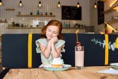愉快的红头发人女孩用闭合的眼睛立即可食的杯形蛋糕和饮料奶昔 库存照片