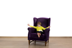 愉快的红色头发孩子坐紫色扶手椅子 免版税库存图片
