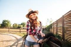 愉快的红头发人妇女女牛仔马鞍为骑乘马做准备 免版税图库摄影
