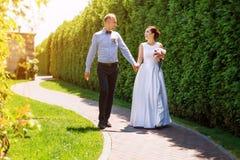 愉快的结婚的年轻婚礼夫妇获得乐趣在公园 新娘和新郎一起,爱和婚姻题材 免版税库存图片
