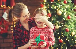 愉快的给圣诞节礼物的家庭母亲和女儿 免版税库存照片