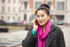 愉快的美丽的亚裔妇女叫由在春天stree的电话 库存照片