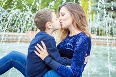 愉快的美丽的享用在喷泉附近的母亲和儿子 库存图片