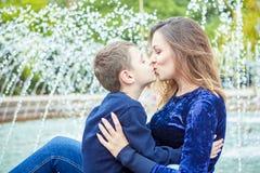 愉快的美丽的享用在喷泉附近的母亲和儿子 免版税库存图片