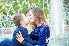 愉快的美丽的享用在喷泉附近的母亲和儿子 免版税库存照片