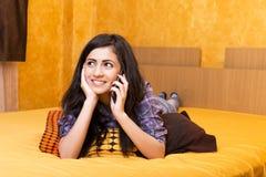 愉快的美丽的十几岁的女孩说在她巧妙的电话里 库存图片