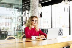 愉快的美丽的卷发白肤金发的年轻女性在使用膝上型计算机的咖啡店,微笑 年轻可爱的妇女自由职业者佩带的gla 库存照片