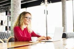 愉快的美丽的卷发白肤金发的年轻女性在使用膝上型计算机的咖啡店,微笑 年轻可爱的妇女自由职业者佩带的gla 免版税图库摄影