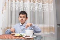 年轻愉快的美丽的吃健康早餐的母亲和她的孩子 库存图片