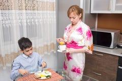 年轻愉快的美丽的吃健康早餐的母亲和她的孩子 免版税库存图片